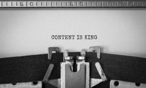 Text 'Content is King' typed on retro typewriter in black and white.